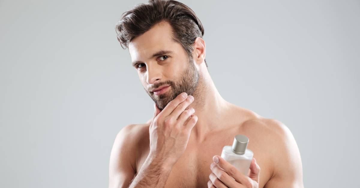 Przystojny mężczyzna dotyka twarzy zzarostem trzymając wdłoni butelkę płynu po goleniu.
