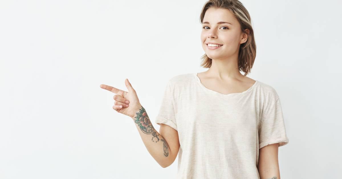 Młoda dziewczyna na jasnym tle, wskazuje coś prawą wytatuowaną ręką.