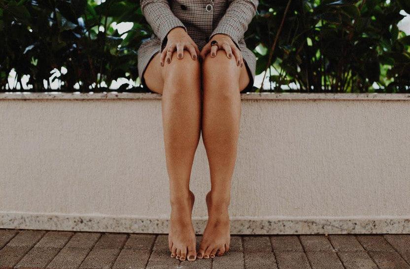kobiece nogi na tle jasnego murka izieleni
