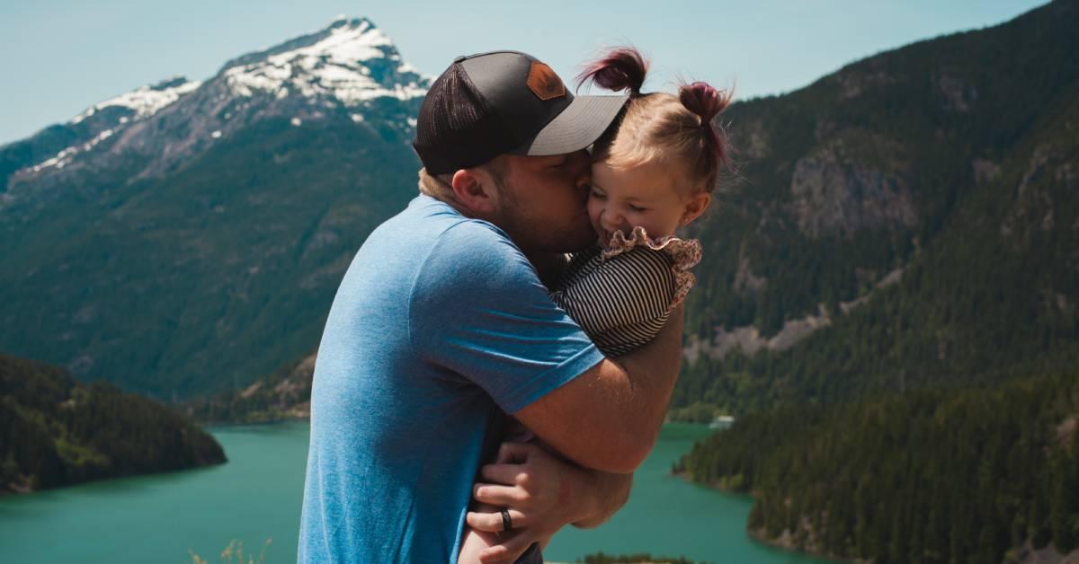 Szczęśliwy tata przytula icałuje córeczkę na tle górskiego pejzażu.