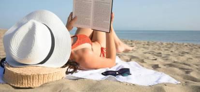 Dziewczyna w kapeluszu opala się na plaży czytając książkę.