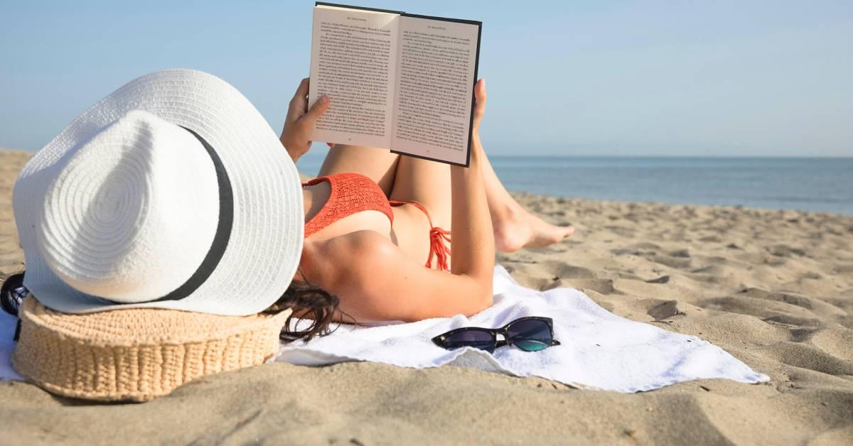 Dziewczyna wkapeluszu opala się na plaży czytając książkę.