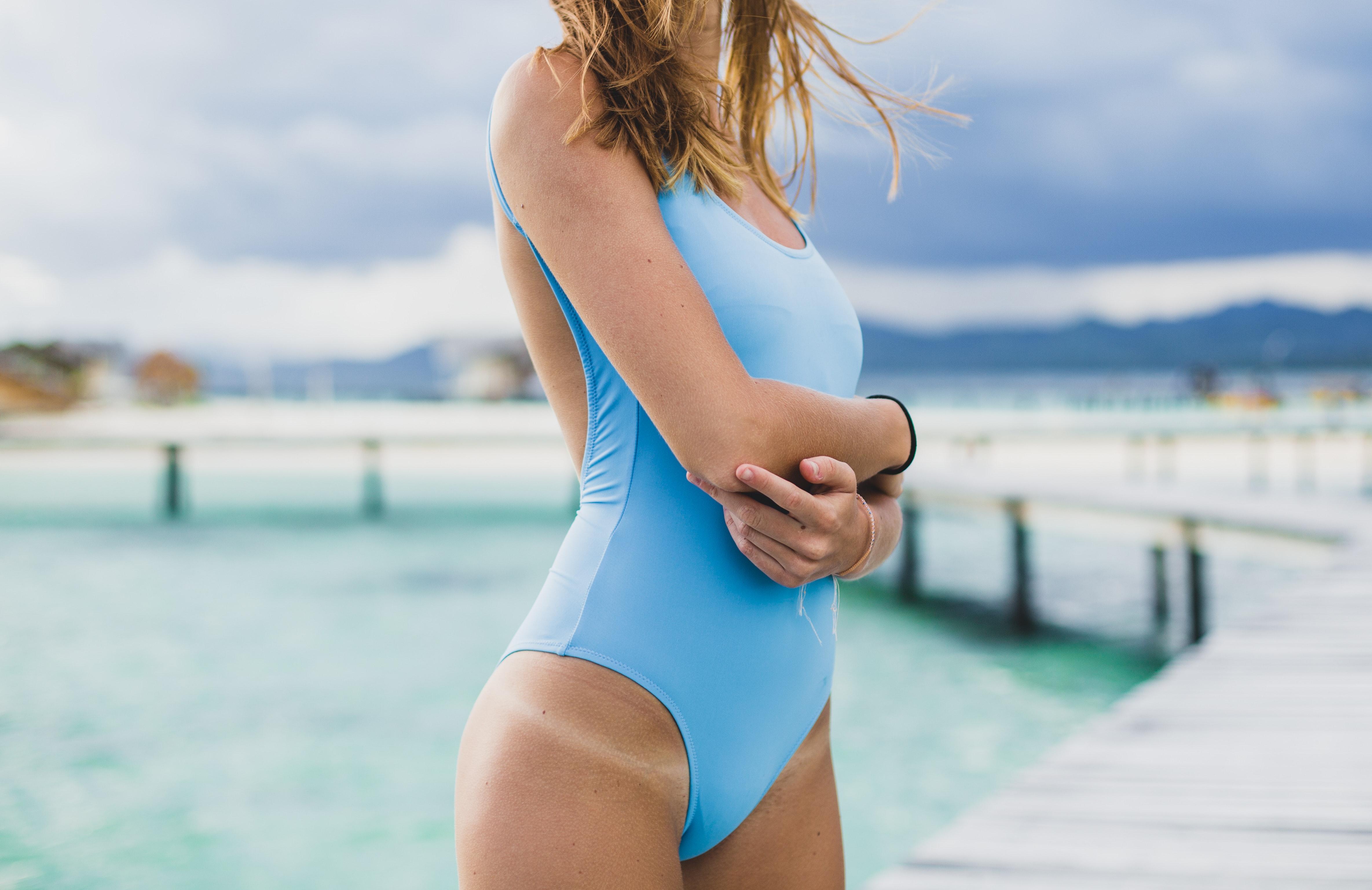 Dziewczyna wniebieskim kostiumie kąpielowym zjasnymi śladami po opalaniu na biodrze.