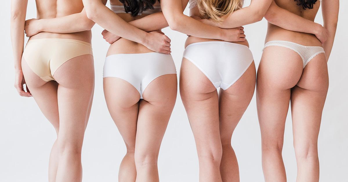 Pośladki czterech dziewczyn wbiałej bieliźnie, widocznych od pasa wdól, które obejmują się na jasnym tle.