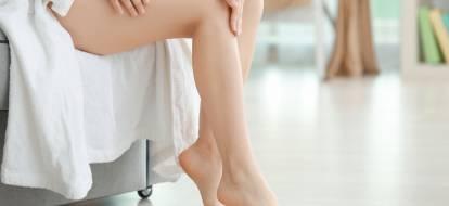 kobiece nogi na tle fotela przykrytego białym ręcznikiem