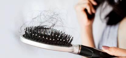Zbliżenie na szczotkę z mnóstwem wyrwanych włosów.