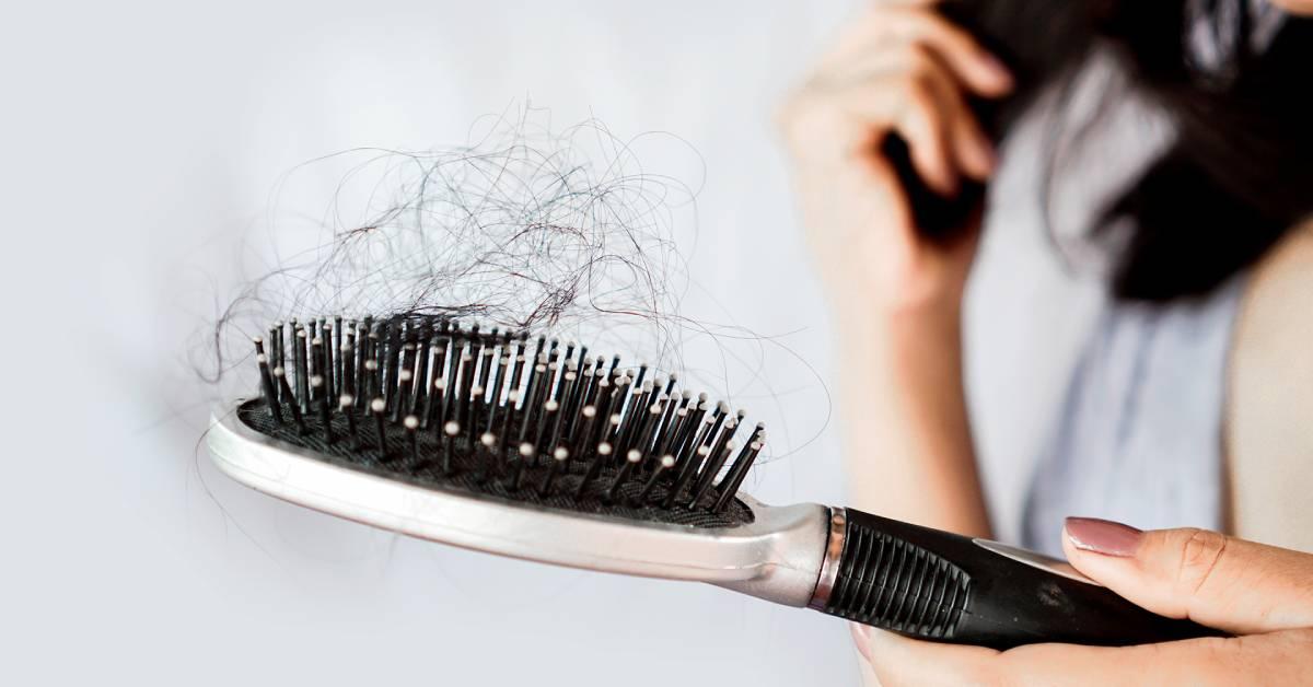 Zbliżenie na szczotkę zmnóstwem wyrwanych włosów.
