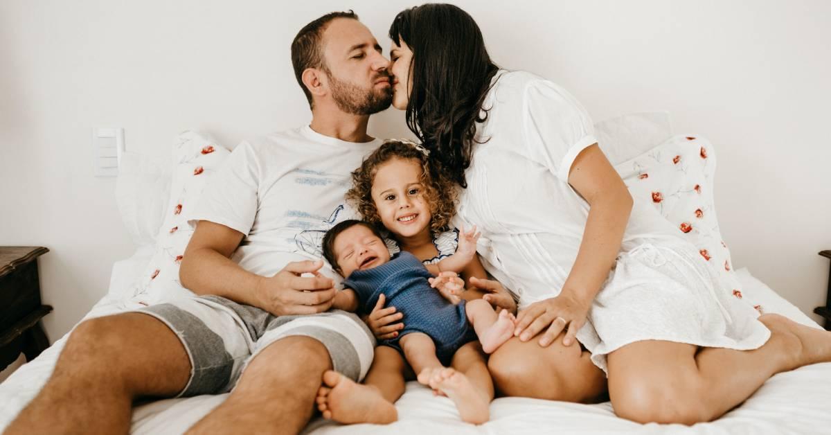 Szczęśliwa rodzina wbiałych t-shirtach na łóżku. Rodzice całują się.