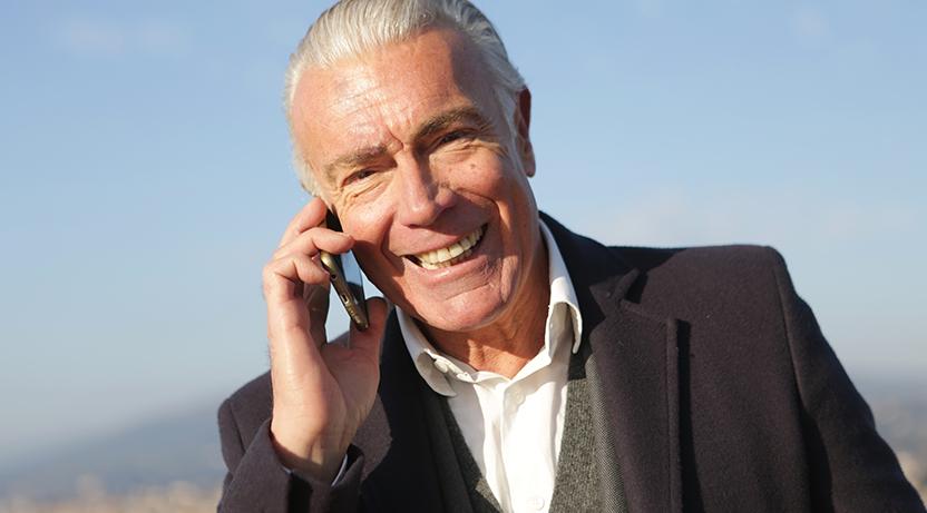 Siwy mężczyzna wgarniturze rozmawia przez komórkę.