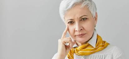 Skupiona starsza kobieta z krótkimi siwymi włosami, dotyka swojej twarzy w zamyśleniu.