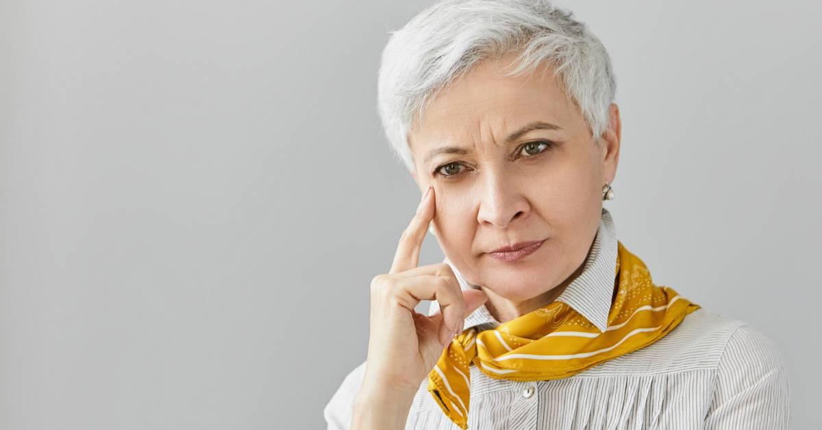Skupiona starsza kobieta zkrótkimi siwymi włosami, dotyka swojej twarzy wzamyśleniu.