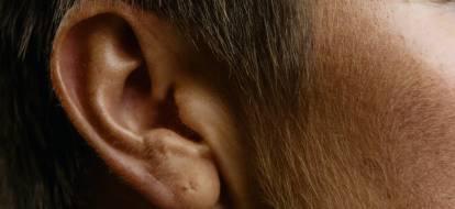 Duże zbliżenie na ucho mężczyzny w dojrzałym wieku.