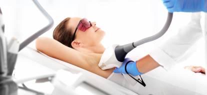 kobieta leżąca na łóżku podczas zabiegu depilacji laserowej