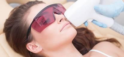 Depilacja laserowa wąsika u uśmiechniętej brunetki w różowych okularach zabiegowych.