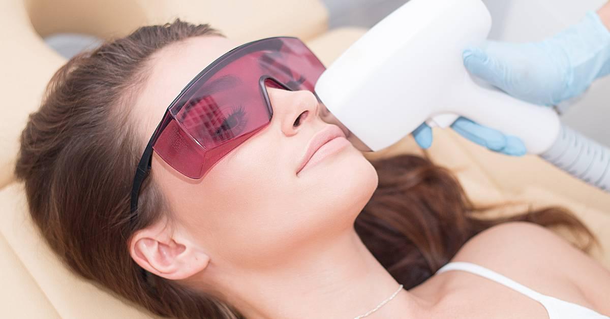 Depilacja laserowa wąsika uuśmiechniętej brunetki wróżowych okularach zabiegowych.