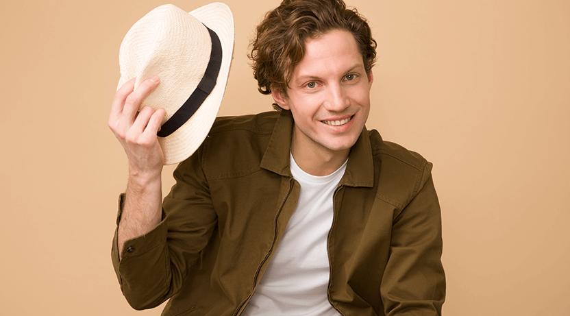 Młody mężczyzna zuśmiechem uchyla kapelusza.