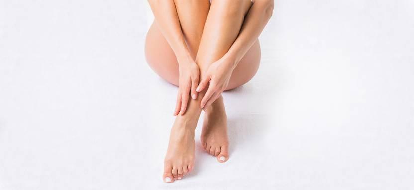 skrzyżowane nogi kobiety zdłońmi na łydkach