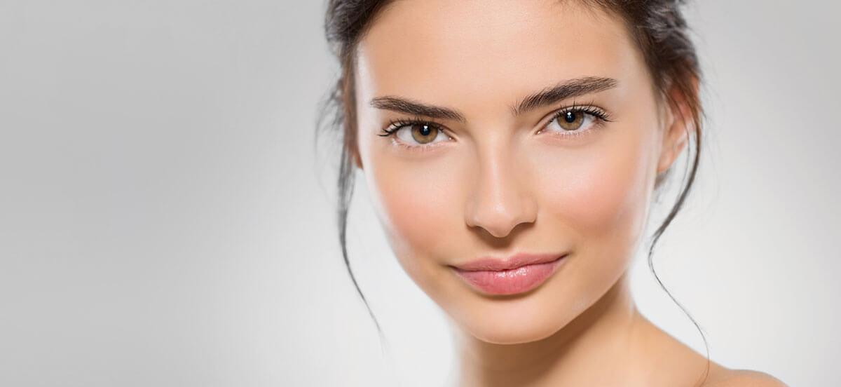 twarz kobiety ze spiętymi ciemnymi włosami idelikatnym makijażem