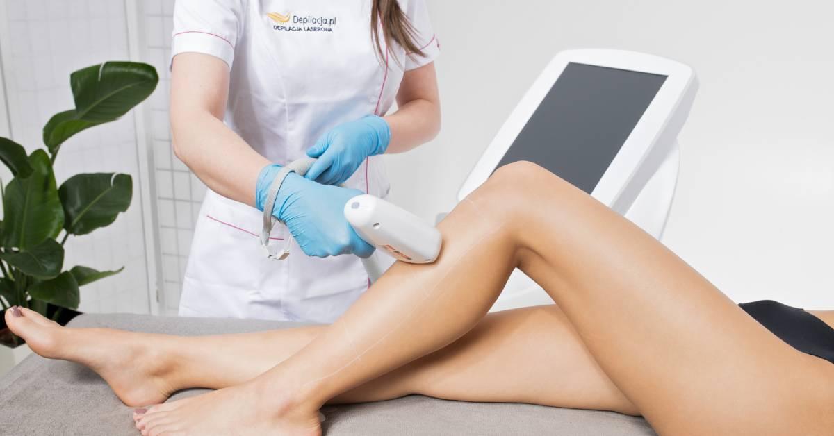 Zbliżenie na łydki, na których kosmetolog przeprowadza depilację laserową.