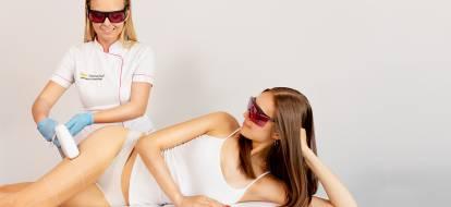 Brunetka leży na boku na leżance w gabinecie kosmetycznym, a kosmetolog przeprowadza zabieg depilacji laserowej na udzie brunetki,