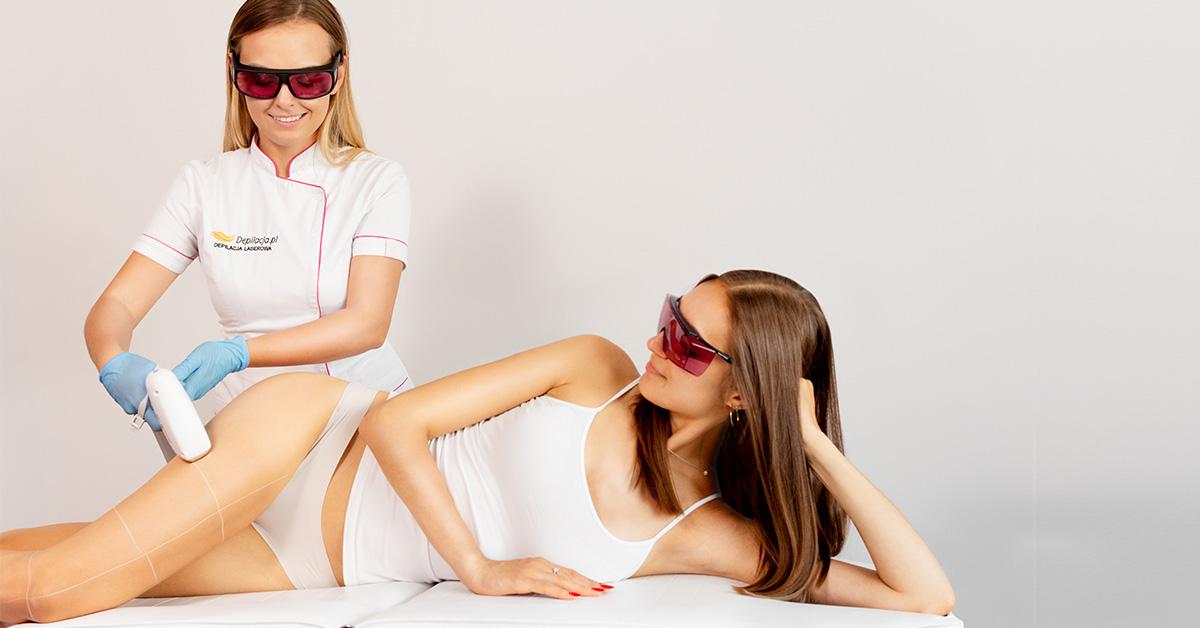 Brunetka leży na boku na leżance wgabinecie kosmetycznym, akosmetolog przeprowadza zabieg depilacji laserowej na udzie brunetki,